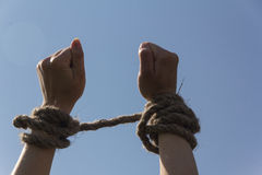 Hands bound by rope. Tied with a rope hands on blue sky background Royalty Free Stock Photo