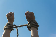 Hands bound by rope. Tied with a rope hands on blue sky background Royalty Free Stock Photography