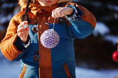 Hands of a boy with christmas ball walking in the winter nature. Playing with snow. Concept happy childhood Royalty Free Stock Image