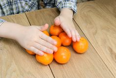 Hands of a boy with oranges Royalty Free Stock Photos