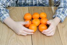 Hands of a boy with oranges Royalty Free Stock Images