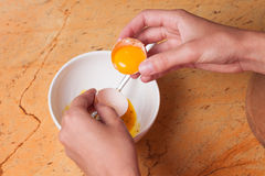 Hands breaking an egg in bowl Stock Photos