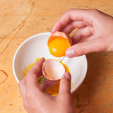 Hands breaking an egg in bowl Royalty Free Stock Images