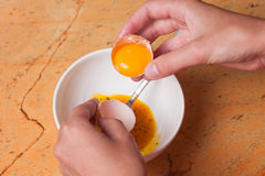 Hands breaking an egg in bowl Royalty Free Stock Photo