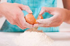 Hands breaking egg into flour Royalty Free Stock Image