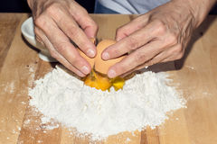 Hands breaking an egg on flour Royalty Free Stock Photography