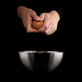 Hands breaking an egg. Royalty Free Stock Image
