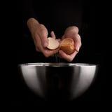 Hands breaking an egg. Stock Image