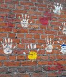 Hands on a brick wall. Stock Images