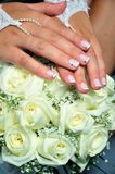 Hands of bride. Wedding manicure on hands of bride, they are laying on wedding flowers Royalty Free Stock Image
