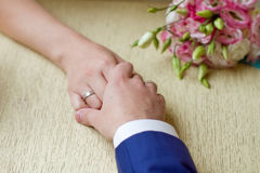 Hands of a bride and a bridegroom, just married, a bridal bouque Royalty Free Stock Images