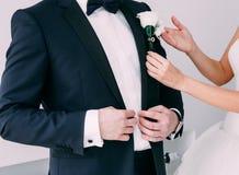 Groom costume butane bride correct hands. Hands the bride corrects the groom`s butanier Stock Images