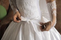 Hands of the bride fasten a bow Royalty Free Stock Photo