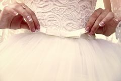 Hands of bride girl hold white bow on wedding dress. Hands of bride girl with manicure hold white bow on wedding dress royalty free stock image
