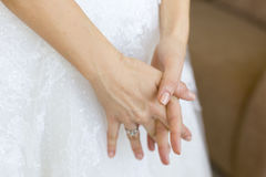 Hands of bride or girl on white wedding dress. Hands of bride or girl with silver engagement ring on white wedding lace dress with rhinestones Royalty Free Stock Photo