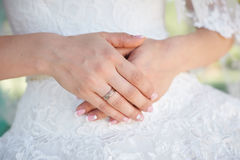 Hands bride with gold ring on background of white dresses Royalty Free Stock Photo