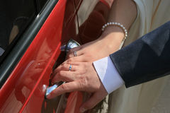 Hands of bride and groom. Newly-married couple opening together a door of the wedding car Stock Images