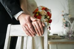 Hands of the bride and groom on the background of an old shabby wooden chair, close-up. The bride is holding a beautiful bouquet royalty free stock photo