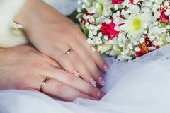 Hands of Bride and Groom. Hands of the groom and the bride and bouquet royalty free stock photography
