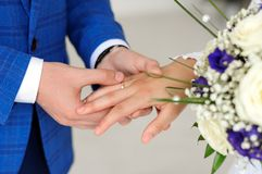 The hands of the bride and groom. The bridegroom will put the ring on the finger of the bride Stock Photos