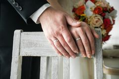 Hands of the bride and groom close-up on the background of an old painted wooden chair. The bride is holding a beautiful bouquet stock images