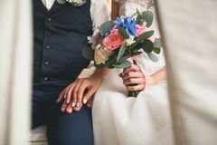 Hands of the bride and groom close-up. The bride is holding a beautiful bouquet of different flowers and green leaves. royalty free stock images