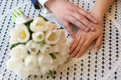 Hands of the bride and groom close-up on table. The palm of the hand touches the groom bride. Hands on lace tablecloths in the cafe. Bouquet blurred. Natural Royalty Free Stock Image