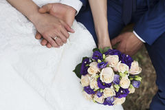Hands of bride and groom with flowers Royalty Free Stock Photos