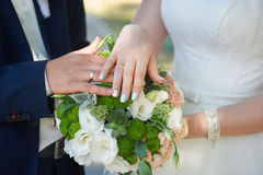 Hands of bride and groom with gold rings on wedding bouquet Royalty Free Stock Photo
