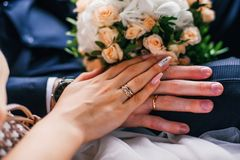 Hands of the bride and groom with gold rings on the wedding day together. On the background of the bouquet Royalty Free Stock Photo