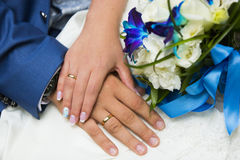 Hands of bride and groom with golden wedding rings and blue and white wedding bouquet Royalty Free Stock Photography
