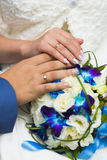Hands of bride and groom with golden wedding rings and blue and white wedding bouquet Royalty Free Stock Photo