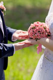 Hands of bride and groom holding a bouquet of pink roses Stock Images