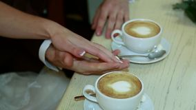 Hands of bride and groom holding a cup of coffee stock video footage