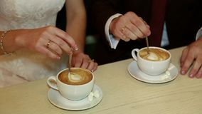 Hands of bride and groom holding a cup of coffee stock footage