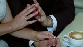 Hands of bride and groom holding a cup of coffee stock video