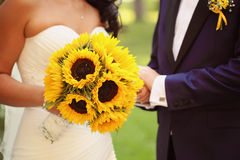 Hands of a bride and groom holding sunflower bouquet Stock Photography