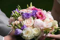 Hands of bride and groom holding  wedding bouquet Stock Photography