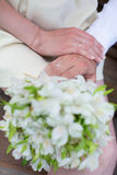 Hands of bride and groom holding wedding bouquet Royalty Free Stock Photo