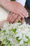 Hands of bride and groom holding wedding bouquet Royalty Free Stock Photography