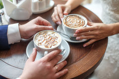 Hands of bride and groom with latte art coffee cup Stock Image