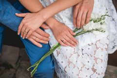 Hands of the bride and groom lie on a bouquet of flowers. The view from the top. Wedding stock photography