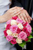 Hands of the bride and groom lying on  bouquet Stock Photography