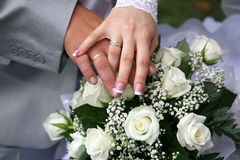 Hands of bride and groom near wedding bouquet Royalty Free Stock Image
