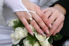 Hands of bride and groom near wedding bouquet Royalty Free Stock Photography