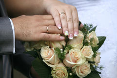 Hands of bride and groom near wedding bouquet Stock Photos