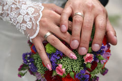 Hands of bride and groom near wedding bouquet Royalty Free Stock Images