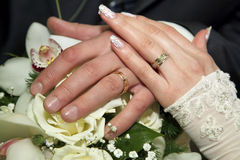 Hands of the bride and groom over wedding bouquet Royalty Free Stock Photography
