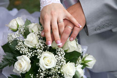 Hands of the bride and groom over wedding bouquet Stock Image
