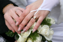 Hands of the bride and groom over wedding bouquet Stock Photography
